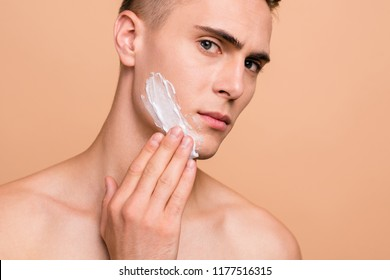 Cropped portrait of handsome, attractive man smearing foam for shave on his face looking at camera isolated on beige background