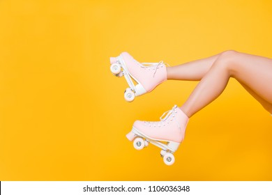 Cropped portrait of legs in pink vintage quad roller skates shoes isolated on yellow background, extreme balance concept, street outside urban lifestyle style, laser hair removal perfect skin