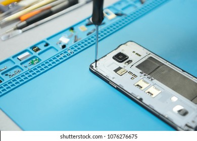 Cropped portrait of repairman holding screwdriver while removing screw on disassembled damaged electronic communication gadget to find faults. People, occupation, repair and electronics concept