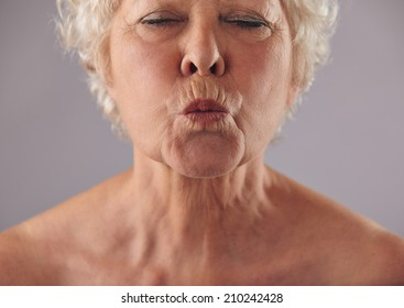 Cropped portrait of senior woman puckering lips. Mature female grimacing against grey background