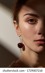 Cropped portrait shot of a young European woman with picked up brown hair. The lady is wearing a stud earring made as a red translucent cherry with a golden tail.