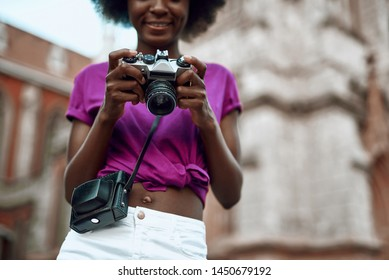 Cropped portrait of smiling lady using camera while walking in the city. Copy space in right side