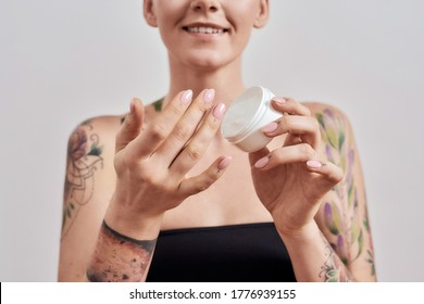 Cropped portrait of smiling tattooed woman trying skin care product, holding white plastic jar of cream or body lotion isolated over grey background. Selective focus on hands and jar. Front view