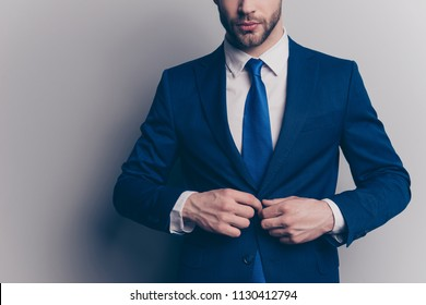 Cropped portrait of stunning, fashionable, cool, virile, rich man with stubble, half face in blue suit fasten button on jacket with two arms, isolated on grey background, going for meeting, date