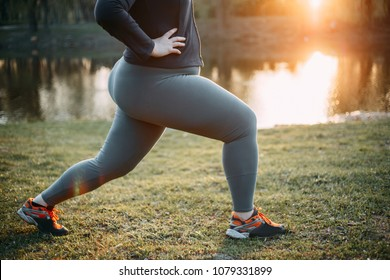 Cropped portrait of woman in sportswear training legs getting ready for running in morning park, copy space. Healthy lifestyle, sport, weight losing, activity concept
