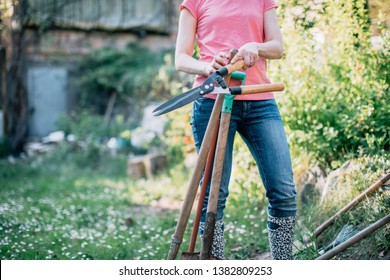 Cropped portrait of the woman standing in the garden with gardening equipment.