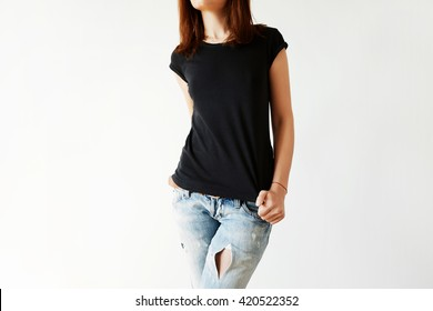 Cropped portrait of young brunette woman with beautiful slim body wearing black T-shirt with copy space for your text or advertising content. Close up of fashionable teenager trying on new clothing