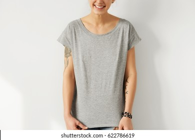 Cropped portrait of young European female with tattooed arms posing against white studio wall, dressed in oversize blank grey t-shirt with copy space for your print. Clothing, style and fashion
