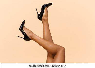 Cropped portrait of young woman 20s wearing black shoes laying with her legs raised isolated over beige background