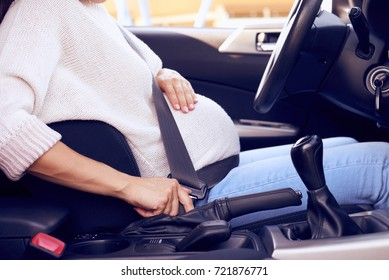 Cropped up of pregnant woman driving the car, buttoned up with seat belt