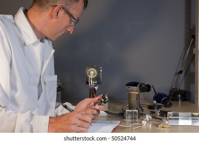 Cropped profile of a researcher in a lab coat and goggles, making notes on an experiment. He is surrounded by scientific equipment. Horizontal format.