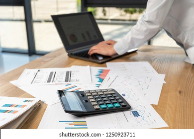 Cropped profile side view photo of lady person in her formal wear shirt she stand behind table in loft interior look at display send receive email use notebook pc gadget with calculator on front