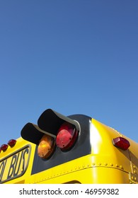 Cropped rear view of a school bus. The taillights are highlighted in the image. Vertical shot.