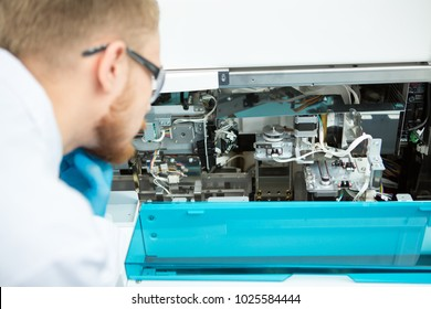 Cropped rearview close up of a male technician lboratory worker examining broken medical equipment copyspace technology machinery science repairing internship problem solution.