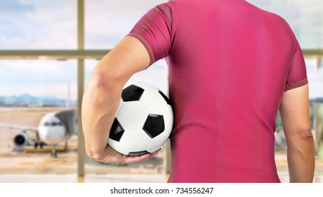 Cropped rearview image of a sports fan holding a soccer ball under his arm with red t-shirt at airport