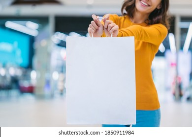 Cropped shop of young brunette woman with beautiful smile holding blank white shopping paperbag while standing in a mall. Mock up, copy space for your text or logo.
