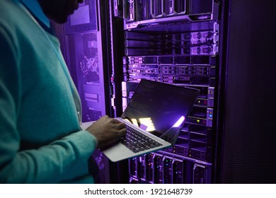 Cropped shot of African American data engineer holding laptop while working with supercomputer in server room lit by blue light, copy space