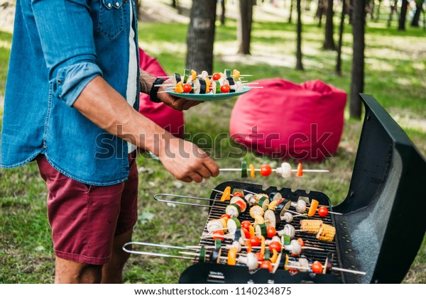 cropped shot of african american man taking grilled vegetables during bbq in park