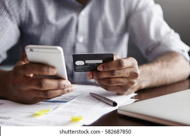 Cropped shot of African-American male paying bill at restaurant with online payment technology via internet, using free wi-fi during breakfast, sitting at table with plastic card and smart phone