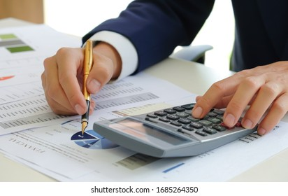 Cropped shot of Analysts use calculators and pointers on graphs to assess the fluctuating stock market situation.
