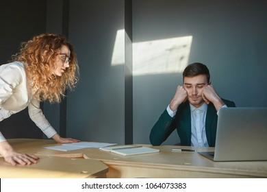 Cropped shot of angry disappointed young female boss in eyeglasses scolding incompetent ineffective male employee, firing him for constant lateness and absenteeism. Two colleagues arguing at office
