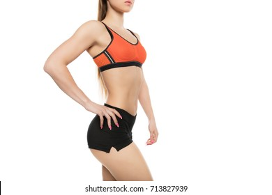 cropped shot of athletic girl in sportswear standing with hand on hip isolated on white