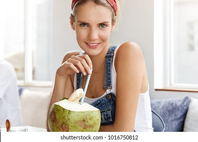 Cropped shot of attractive woman in casual clothing enjoys coconut cocktail in local cafeteria, being pleased, sips through straw. Relaxation, summer holidays, leisure and lifestyle concept.
