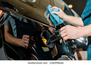 cropped shot of auto mechanic cleaning car with rag at auto repair shop