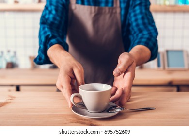 cropped shot of barista in apron holding cup of coffee on counter in cafe