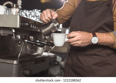 cropped shot of barista in apron pouring milk into coffee while preparing it in restaurant
