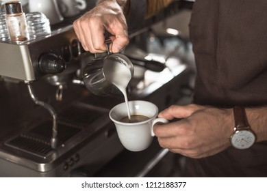 cropped shot of barista pouring milk into coffee while preparing it in restaurant