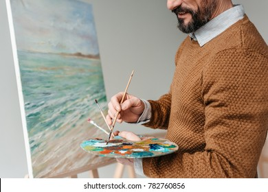 cropped shot of bearded man holding palette and painting on easel at art class