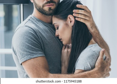 cropped shot of bearded man hugging and supporting young sad woman