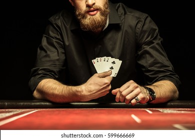 Cropped shot of bearded man showing poker cards isolated on black