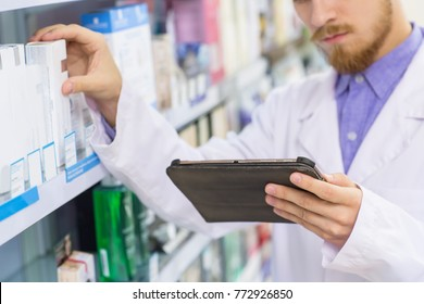 Cropped shot of a bearded pharmacist in medical coat taking an item from a shelf at the drugstore while using digital tablet technology online shopping ordering products pharmacy chemist medicine