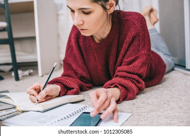 Cropped shot of beautiful housewife lying on the floor, using laptop managing domestic budget, making notes with pencil, calculate on smart phone, paper and documents. Business woman working at home.