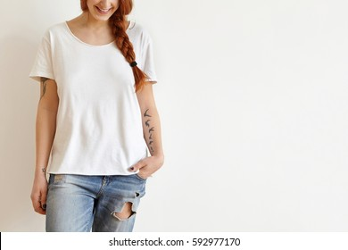 Cropped shot of beautiful stylish young redhead woman with braid and tattoos smiling joyfully dressed in white oversize t-shirt, keeping hand in pocket of her trendy blue ragged jeans. Horizontal