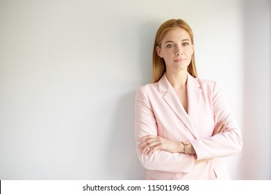 Cropped shot of beautiful young woman wearing blazer and looking at camera while standing with folded arms at the wall.