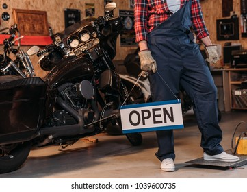 cropped shot of bike repair station worker holding open signboard at garage