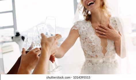 Cropped shot of bride in wedding dress and her friends drinking champagne in bridal boutique. Focus on female hands toasting champagne in wedding clothing shop.