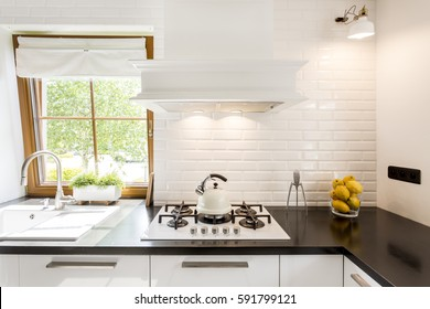 Cropped shot of a bright kitchen room designed in white with a black countertop