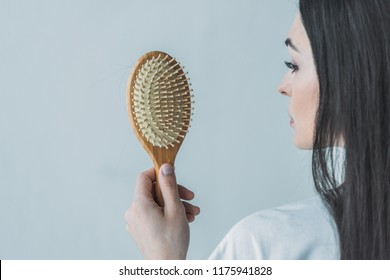 cropped shot of brunette woman holding hairbrush with fallen hair isolated on grey
