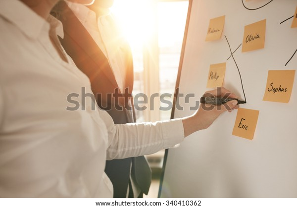 Cropped shot of business people making pairs of employees for making efficient sales team. Woman pairing sticky notes on whiteboard with marker pen.