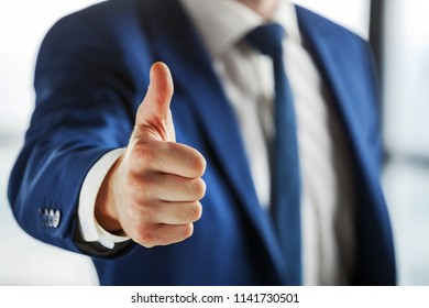 Cropped shot of business person showing thumb up.