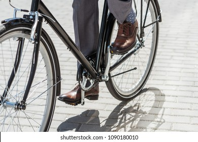 cropped shot of businessman in classic shoes riding vintage bicycle