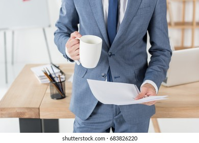 cropped shot of businessman with coffee cup and papers standing at workplace