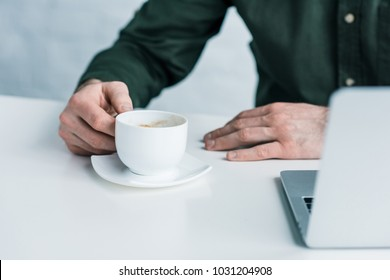 cropped shot of businessman with cup of coffee at workplace
