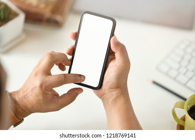 Cropped shot of businessman hand holding blank screen mobile phone at office