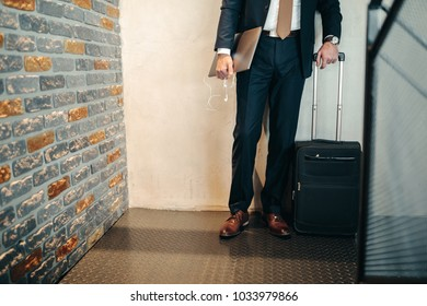 Cropped shot of a businessman holding a suitcase and a computer