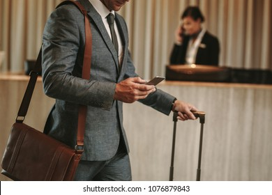 cropped shot of businessman in hotel lobby with mobile phone and luggage. Male business traveler arriving at his hotel, with focus on hands holding smart phone.